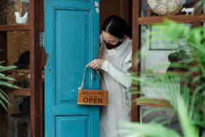 woman in face mask putting out open sign on front door