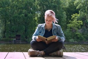 woman sitting next to pond reading on dock
